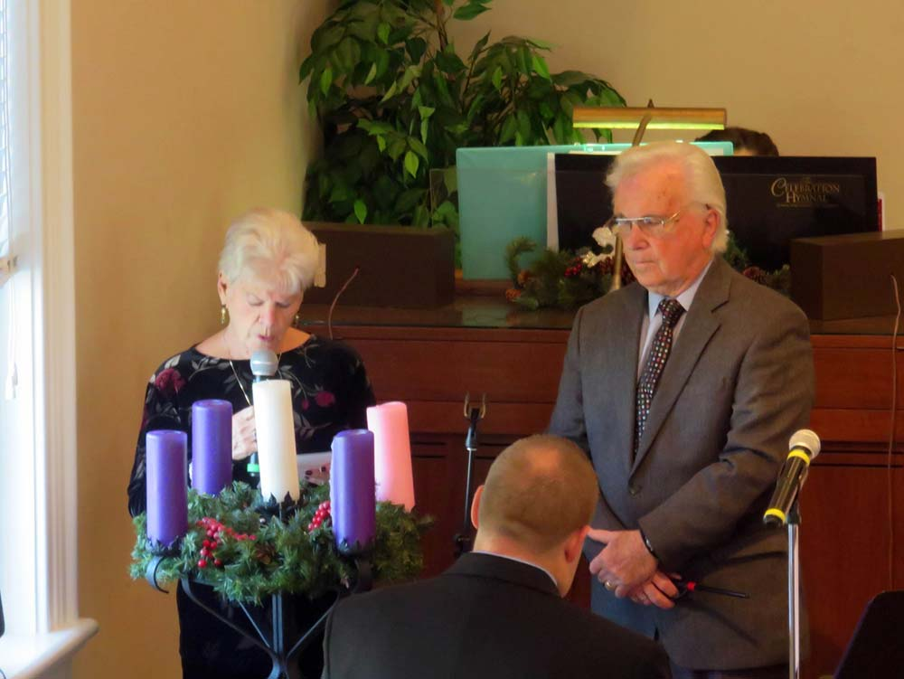 Woman talkkng in microphone and a man praying next to her.