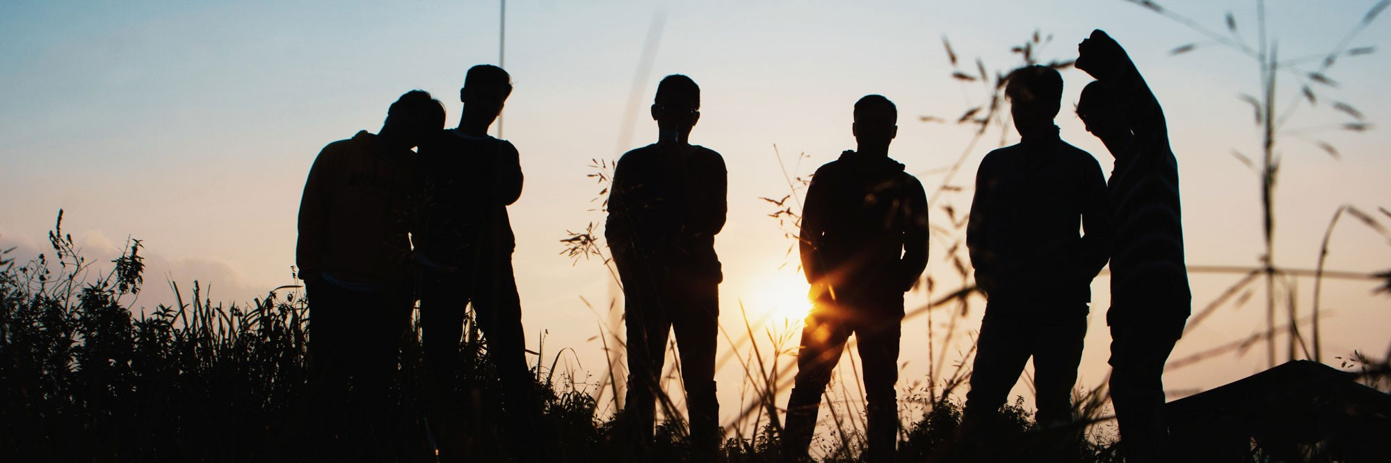 Young boys or men standing in a field in silhouette