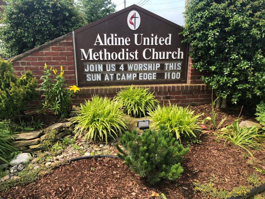 Aldine sign with plants and mulch